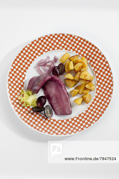 Sherry herring with roasted potatoes  onion and grapes on plate