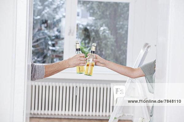 Menschliche Hände toasten Bierflaschen