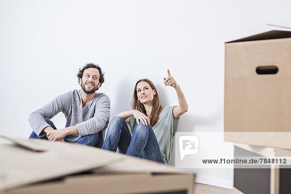 Paar auf dem Boden sitzend mit Umzugskartons
