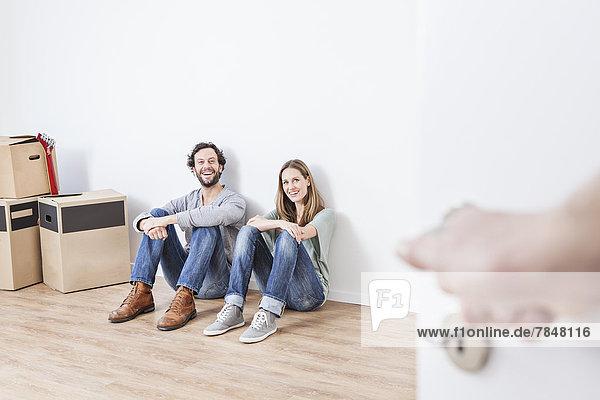 Paar auf dem Boden sitzend  lächelnd