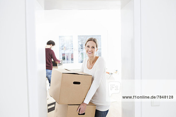 Frau beim Entladen von Kisten in ihrem neuen Haus  während der Mann im Hintergrund lächelt.