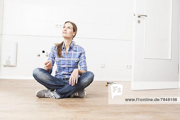 Frau auf dem Boden sitzend  aufblickend
