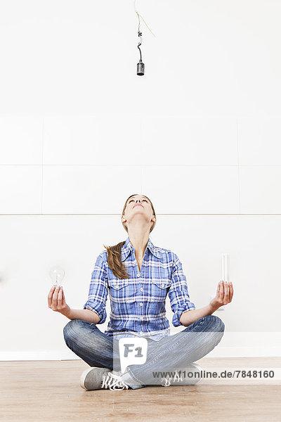 Frau auf dem Boden sitzend mit Glühbirnen