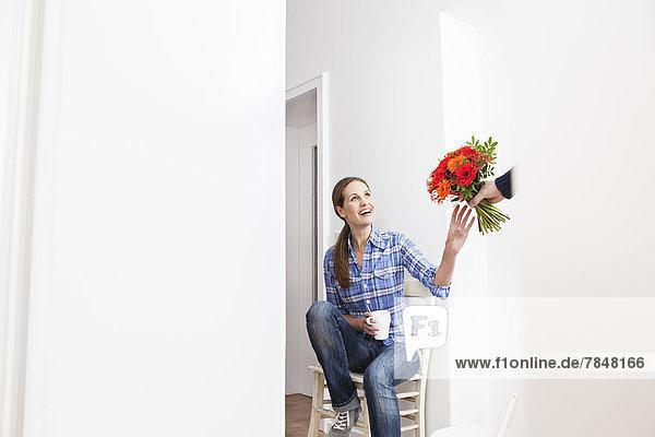 Menschliche Hand  die der Frau Blumenstrauß schenkt  lächelnd