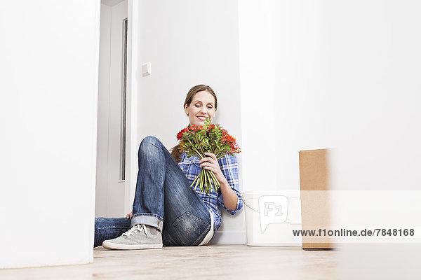 Frau hält Blumenstrauß  lächelnd