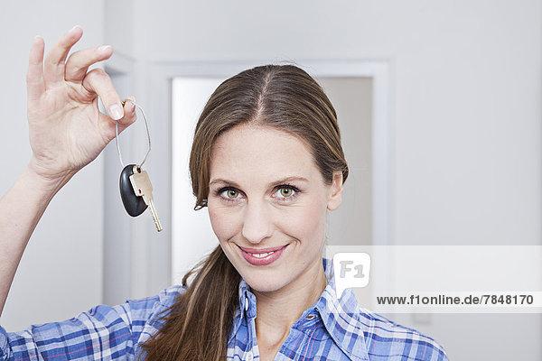 Porträt einer Frau mit Schlüssel  lächelnd