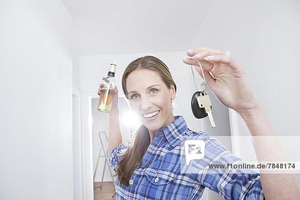 Frau mit Bierflasche und Schlüssel  lächelnd