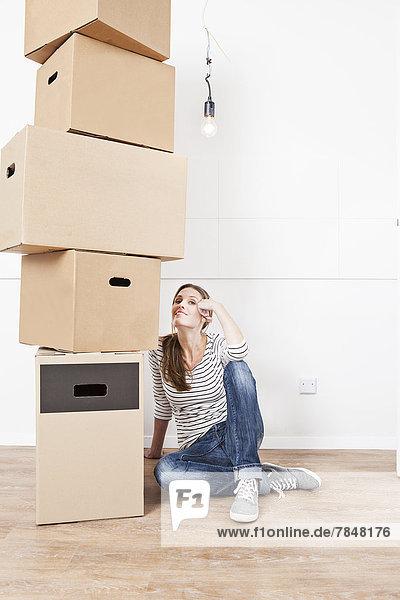 Frau sitzt auf dem Boden neben einem Stapel Pappkartons