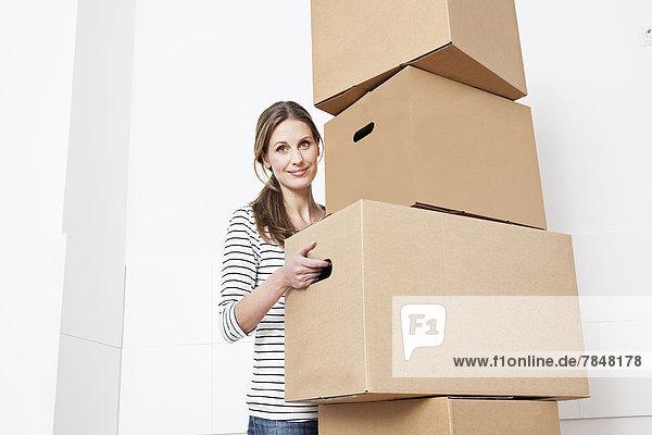 Frau trägt Kartonstapel  lächelnd