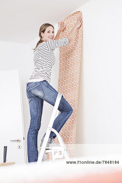 Frau klebt Tapete an die Wand