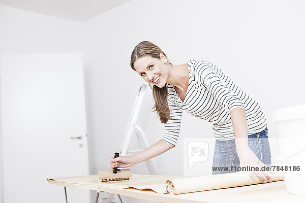 Woman applying glue on wallpaper