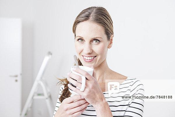 Porträt einer Frau  die den Becher hält  lächelnd