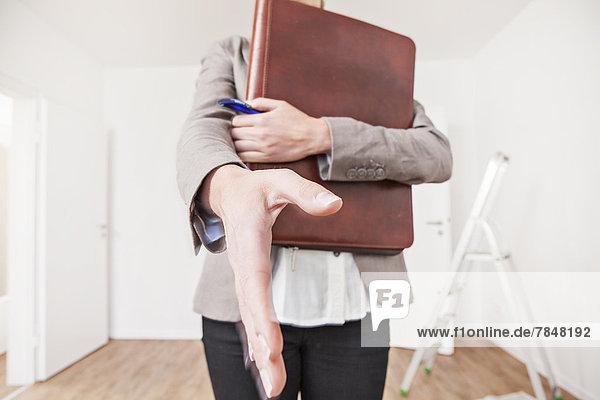 Frau mit Feile und Stift nähert sich zum Händeschütteln