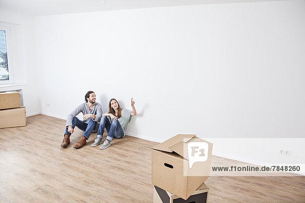 Paar auf dem Boden sitzend und auf die Wand zeigend
