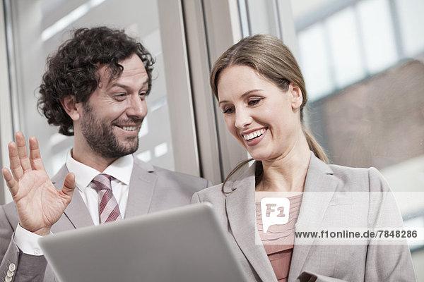 Deutschland  Nordrhein-Westfalen  Köln  Geschäftspaar mit Laptop  lächelnd