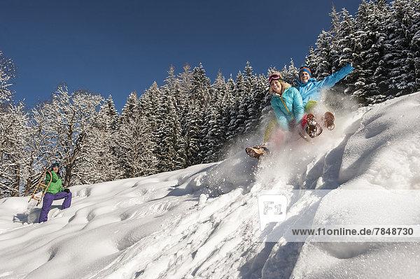 Österreich  Salzburg  Junge Männer und Frauen mit Schlitten im Schnee am Altenmarkt Zauchensee
