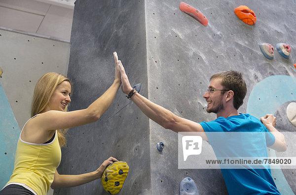 Junger Mann und Frau  die oben hoch fünf geben  lächelnd
