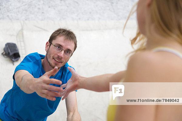 Junger Mann hilft Frau beim Klettern