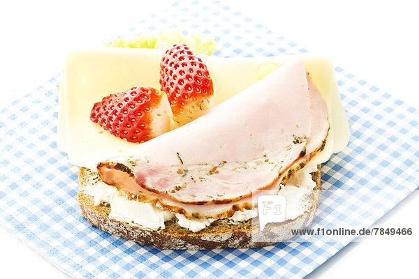 Fitness-Sandwich mit Frischkäse  Käse und Schinken-Erdbeer-Scheibe auf weißem Grund  Nahaufnahme