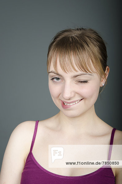 Porträt einer jungen Frau mit Augenzwinkern  Nahaufnahme  Mund