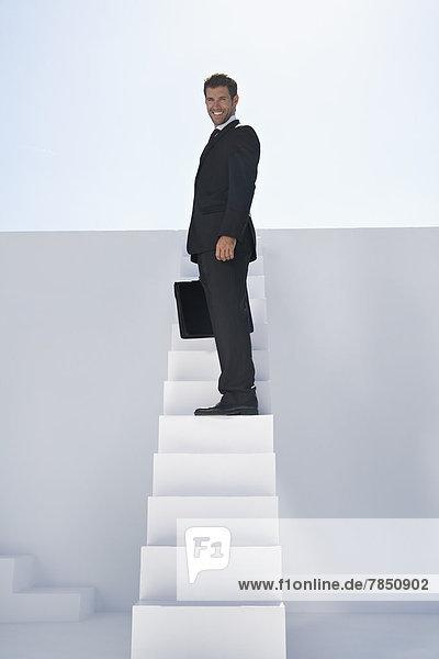 Geschäftsmann im schwarzen Anzug mit Aktentasche auf Treppe stehend  lächelnd  Portrait