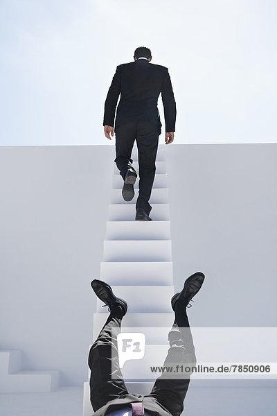 Geschäftsleute  die herunterfallen und eine weiße Treppe hinaufgehen.