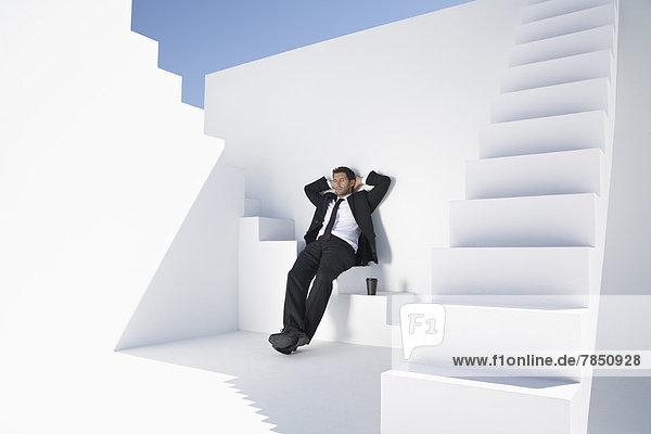 Geschäftsmann im schwarzen Anzug auf der Treppe sitzend