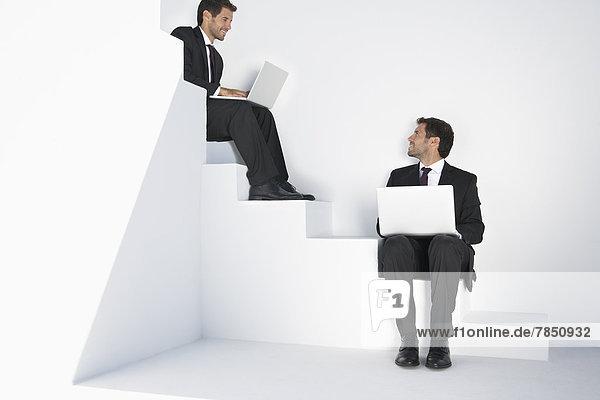 Geschäftsleute sitzen auf einer Treppe und benutzen einen Laptop.