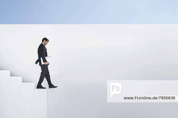 Geschäftsmann im schwarzen Anzug mit Laptop im Treppenabgang
