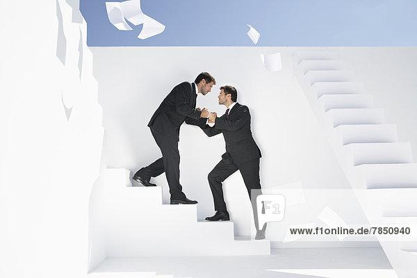Geschäftsleute  die auf einer Treppe stehen und kämpfen.