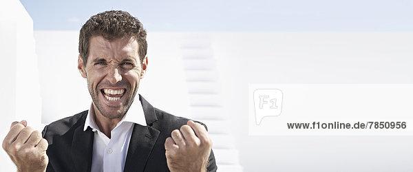 Porträt eines Geschäftsmannes im schwarzen Anzug  lächelnd