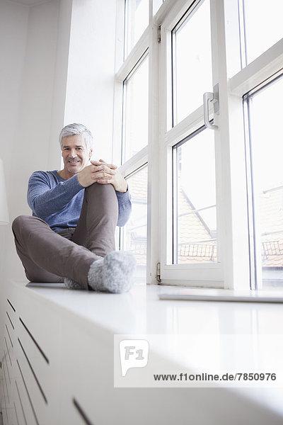 Porträt eines reifen Mannes am Fenster sitzend  lächelnd