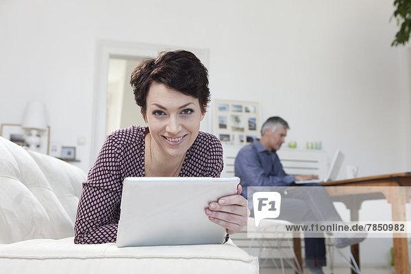 Frau hält digitales Tablett  während der Mann den Laptop im Hintergrund benutzt.