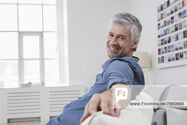 Portrait of mature man sitting on couch  smiling
