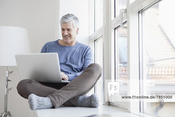 Mature man sitting at window and using laptop