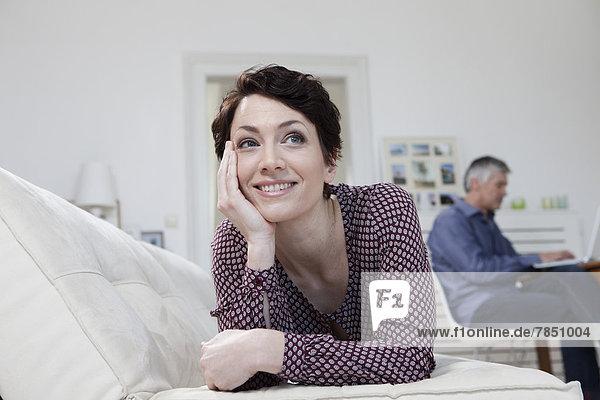 Frau stützt sich auf das Sofa  während der Mann den Laptop im Hintergrund benutzt