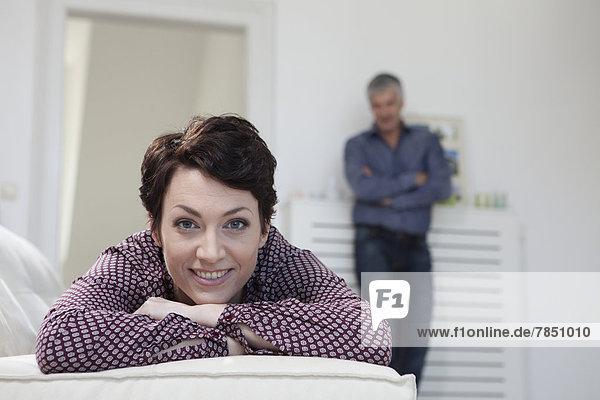 Porträt einer Frau  die auf dem Sofa liegt  während der Mann im Hintergrund steht.