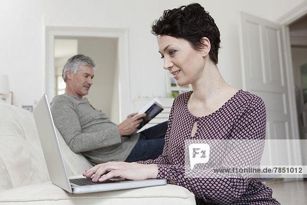 Frau mit Laptop beim Lesen von Büchern im Hintergrund