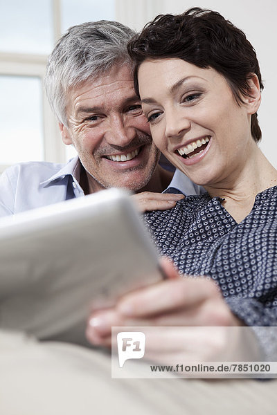 Germany  Bavaria  Munich  Couple using digital tablet at home  smiling