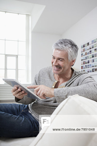 Mature man using digital tablet on couch  smiling