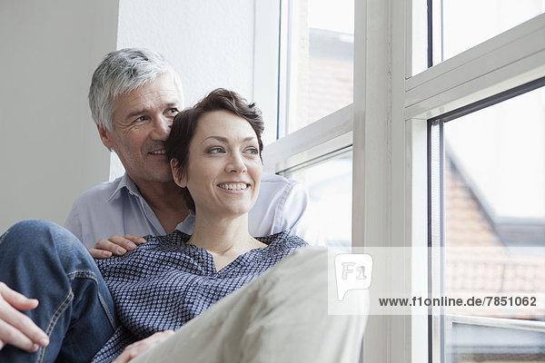 Deutschland  Bayern  München  Paar am Fenster sitzend  lächelnd