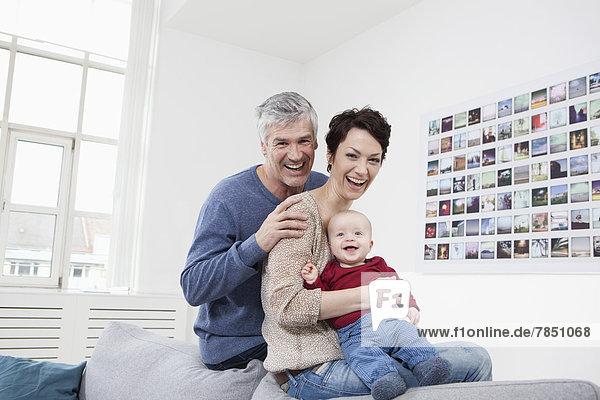 Deutschland  Bayern  München  Porträt der Familie auf der Couch sitzend  lächelnd