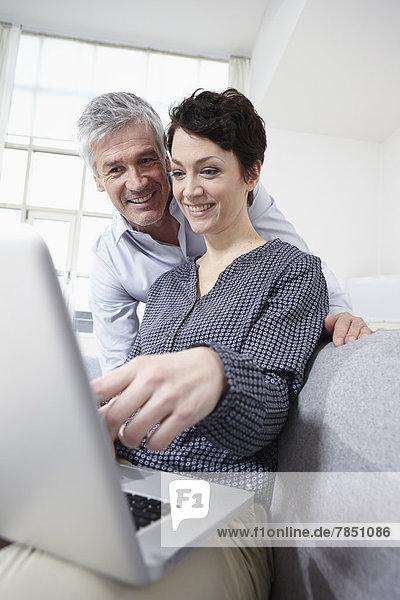 Deutschland  Bayern  München  Paar mit Laptop zu Hause  lächelnd
