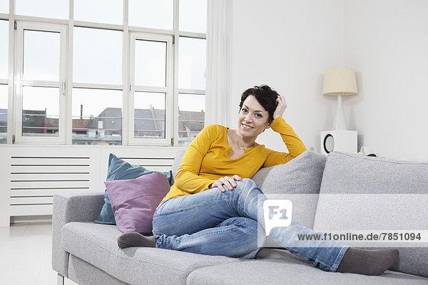 Porträt einer erwachsenen Frau auf der Couch sitzend  lächelnd