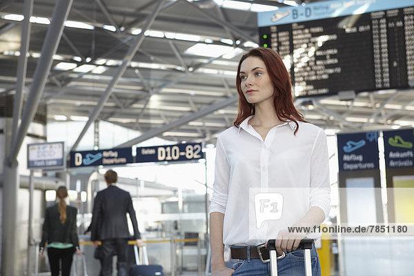 Junge Frau mit Gepäck am Flughafen