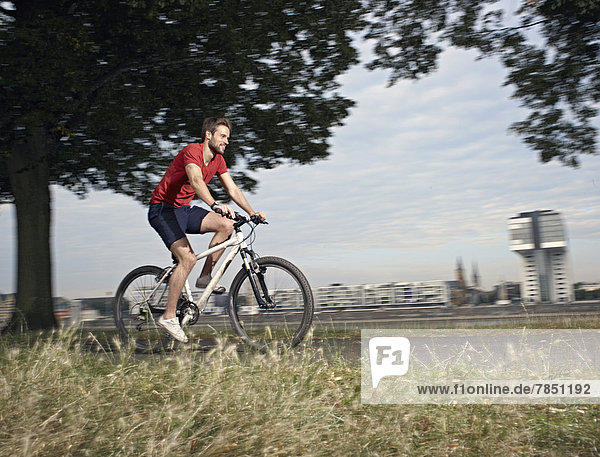 Mid adult man riding bicycle