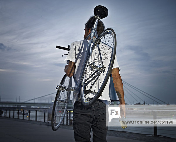 Junger Mann mit Fahrrad auf der Schulter mit Bierflasche
