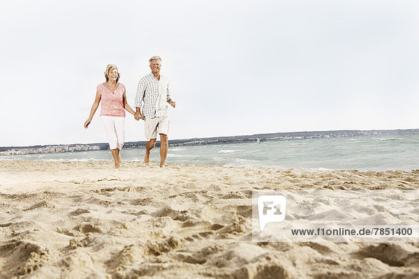Spanien  Seniorenpaar zu Fuß am Strand von Palma de Mallorca