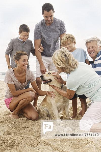 Spanien  Familie mit Hund am Strand von Palma de Mallorca  lächelnd
