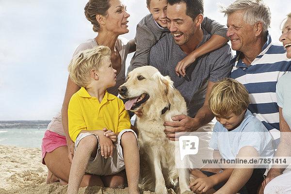 Spanien  Familie am Strand von Palma de Mallorca sitzend  lächelnd